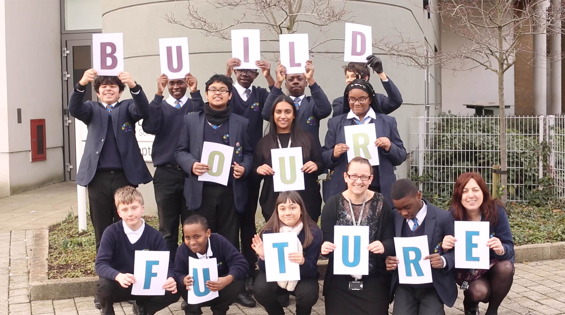 Video thumbnail. Children holding 'BUILD OUR FUTURE' sign